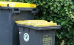 """Ein Bildausschnitt von zwei gelben Tonnen (schwarzer Tonnen-Körper mit gelbem Deckel). Die rechte Tonne trägt die Aufschrift """"Gelbe Tonne""""."""